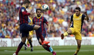 Barcelona's Gerard Pique, left, and Atletico's Koke, right, challenge for the ball during a Spanish La Liga soccer match between FC Barcelona and Atletico Madrid at the Camp Nou stadium in Barcelona, Spain, Saturday, May 17, 2014. (AP Photo/Emilio Morenatti)