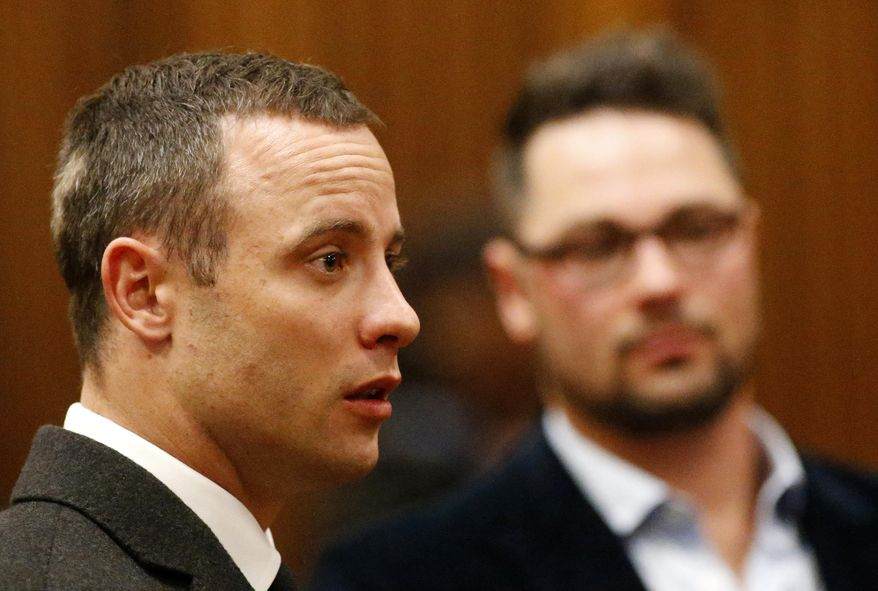 Oscar Pistorius, listens as a court ruling is handed down that he would undergo psychiatric evaluation in Pretoria, South Africa, Tuesday, May 20, 2014. Pistorius is charged with the shooting death of his girlfriend Reeva Steenkamp on Valentine's Day in 2013. At back right is brother Carl Pistroius. (AP Photo/Siphiwe Sibeko, Pool)