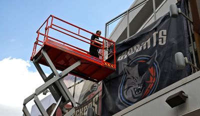 Installers Mariano Simmons, left, and Chaz Lisk, in preparation for Tuesday's official name change, take down Charlotte Bobcats branding at Time Warner Cable Arena in exchange for Charlotte Hornets signs on Monday, May 19, 2014, in Charlotte, N.C. (AP Photo/The Charlotte Observer, Jeff Siner)