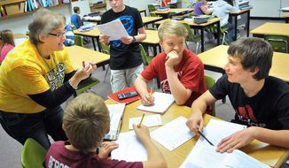 File -- In this Oct. 18, 2013 file photo Chippewa Falls, Wis., Middle School Teacher Melissa Rasmus, left, works with 8-grade students, from top: Taylor Detlaff, 13; Mitchell Haglund, 14; Logan Kurtenbach,14 and Chase Bergeron, 14, during a math class at the Wisconsin school. Officials said Tuesday, May 20, 2014 that more 2,800 students have applied to receive a taxpayer-funded voucher to attend private and religious schools in Wisconsin next year, the second year of the statewide voucher program. That is more than double the enrollment cap of 1,000. (AP Photo/Eau Claire Leader-Telegram/Shane Opatz, File)