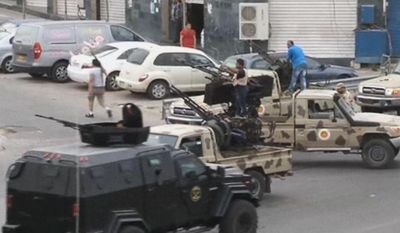 ** FILE ** In this image made from video provided by the Libyan national army via AP Television, Tripoli joint security forces on vehicles with heavy artillery stand guard on the entrance road to the parliament area after troops of Gen. Khalifa Hifter targeted Islamist lawmakers and officials at the parliament in Tripoli, Libya, Sunday, May 18, 2014. (AP Photo/Libyan national army)