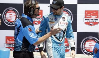 In this May 18, 2014 photo James Hinchcliffe, of Canada, talks with a crewman after his qualification run for the Indianapolis 500 IndyCar auto race at the Indianapolis Motor Speedway in Indianapolis. A week ago, there were questions that Hinchcliffe would be able to race in the Indianapolis 500 after suffering a concussion in the Grand Prix of Indianapolis. The 27-year old Canadian is not only cleared to drive, he's second on the grid for the most famous race in IndyCar (AP Photo/Tom Strattman)