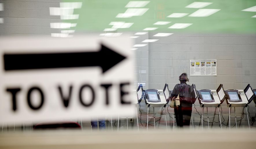 In this May 16, 2014, file photo, a voter casts her ballot at a polling site during early voting for Georgia's upcoming May 20 primary election in Atlanta. (AP Photo/David Goldman) ** FILE **