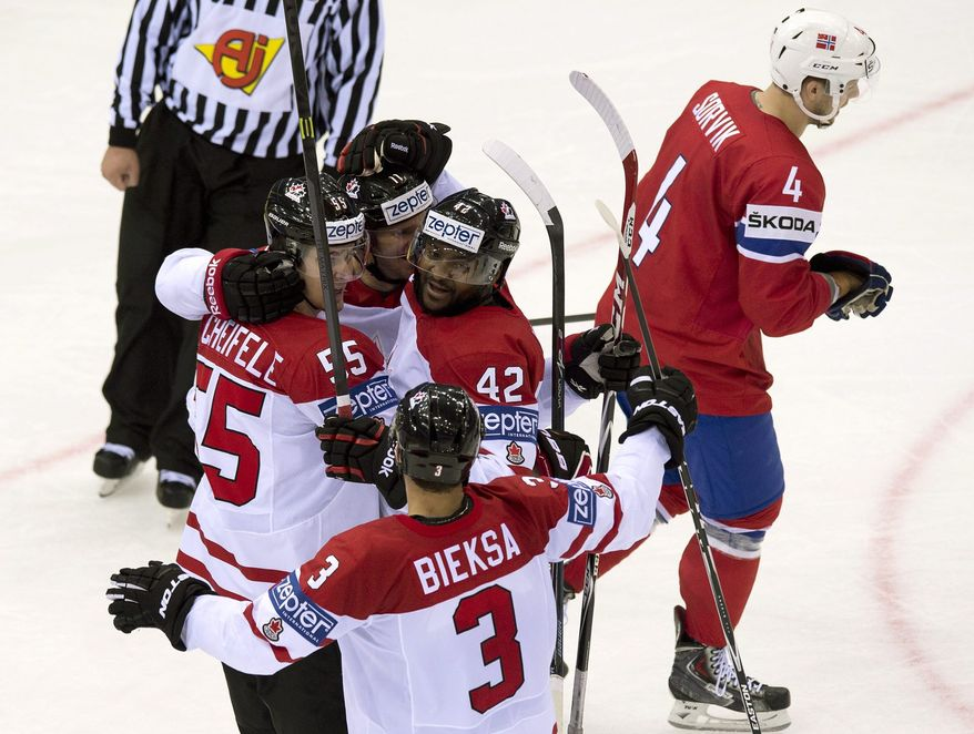 Team Canada Joel Ward (42), center, is congratulated by teammate Mark Scheifele (55), Jonathan Huberdeau, and Kevin Bieksa after scoring the winning goal against Norway during third period action Tuesday, May 20, 2014 at the IIHF World Hockey Championship in Minsk,  Belarus. Norway player Daniel Sorvik skates away. (AP Photo/The Canadian Press, Jacques Boissinot)