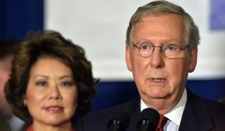 Kentucky Sen. Mitch McConnell, right, addresses his supporters as his wife Elaine Chao looks on following his victory in the republican primary Tuesday, May 20, 2014, at the Marriott Louisville East in Louisville, Ky. (AP Photo/Timothy D. Easley)