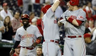 Cincinnati Reds' Todd Frazier, right, celebrates with Chris Heisey, center, as Brandon Phillips (4) walks near, after Frazier hit a two-run homer during the 15th inning of a baseball game against the Washington Nationals at Nationals Park, Monday, May 19, 2014, in Washington. The Reds won 4-3 in 15 innings. (AP Photo/Alex Brandon)