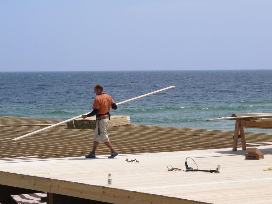 In this May 12, 2014 photo, a worker carries lumber to the edge of a pier being rebuilt in Seaside Park N.J. after a devastating fire last September. As the second summer after the Oct. 29, 2012 storm arrives, some at the Jersey shore are getting their lives back together, while for others, getting back to normal is still a long way off.(AP Photo/Wayne Parry)
