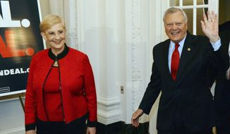 Georgia Gov. Nathan Deal enters a ballroom to give his victory speech as first lady Sandra Deal stands by his side at his election night party at the Georgian Terrace Hotel in Atlanta, Tuesday, May 20, 2014. (AP Photo/Atlanta Journal-Constitution, Kent D. Johnson)