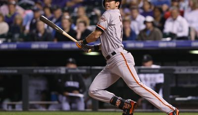 San Francisco Giants' Tyler Colvin follows the flight of his RBI-double against the Colorado Rockies in the ninth inning of the Rockies' 5-4 victory in a baseball game in Denver on Tuesday, May 20, 2014. (AP Photo/David Zalubowski)