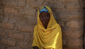 ** FILE ** In this photo taken Sunday, May 18, 2014, Joy Bishara, one of the school girls that escaped being kidnapped by Islamist extremists by jumping off a truck, is photographed outside her home, in Chibok, Nigeria. More than 200 schoolgirls were kidnapped from a school in Chibok in Nigeria's north-eastern state of Borno on April 14. Boko Haram claimed responsibility for the act. (AP Photo/Sunday Alamba)