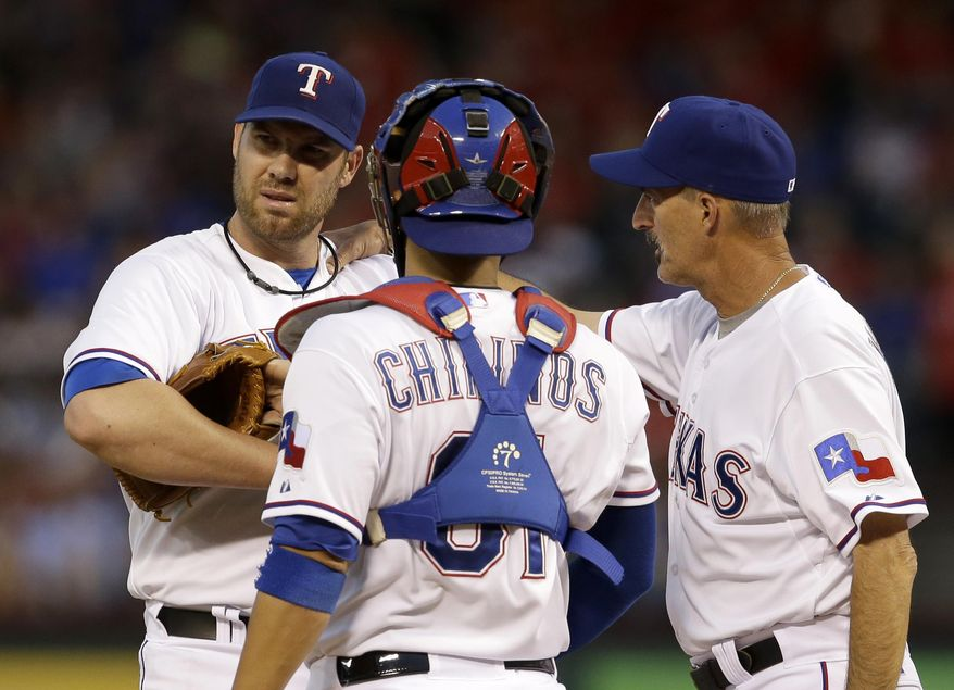 Texas Rangers' Colby Lewis, left, gets a visit on the mound from Robinson Chirinos (61) and pitching coach Mike Maddux, right, after the Seattle Mariners loaded the bases in the fourth inning of a baseball game, Tuesday, May 20, 2014, in Arlington, Texas. (AP Photo/Tony Gutierrez )