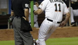 Miami Marlins manager Mike Redmond (11) kicks dirt as he protests a strike out called on Adeiny Hechavarria as home plate umpire Will Little looks on in the sixth inning of a baseball game against the Philadelphia Phillies in Miami, Tuesday, May 20, 2014. The Phillies won 6-5. (AP Photo/Alan Diaz)