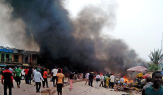 Smoke rises after a bomb blast at a bus terminal in Jos, Nigeria, Tuesday, May 20, 2014. Two explosions ripped through a bustling bus terminal and market frequented by thousands of people in Nigeria's central city of Jos on Tuesday afternoon, and police said there are an unknown number of casualties. The blasts could be heard miles away and clouds of black smoke rose above the city as firefighters and rescue workers struggled to reach the area as thousands of people fled. (AP Photo/Stefanos Foundation)