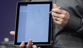 Panos Panay, Microsoft's vice president for Surface Computing, holds an electronic stylus that works with the Surface Pro 3 and Final Draft software at a media preview, Tuesday, May 20, 2014 in New York. The device will have a screen measuring 12 inches diagonally, up from 10.6 inches in previous models. Microsoft says it's also thinner and faster than before.  (AP Photo/Mark Lennihan)
