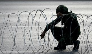 A Thai soldier checks barbed wire while guarding a road near pro-government demonstration site on the outskirts of Bangkok, Thailand Wednesday, May 21, 2014. Thailand's army chief Gen. Prayuth Chan-ocha assumed the role of mediator Wednesday by summoning the country's key political rivals for face-to-face talks one day after imposing martial law. The meeting ended without any resolution, however, underscoring the profound challenge the army faces in trying to end the country's crisis. (AP Photo/Wason Wanichakorn)