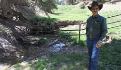 Otero cattle rancher association president Gary Stone talks near a fence Weed, New Mexico, Thursday, May 15, 2014. The Otero County Cattleman's Association is pitted against the National Forest Service over a fence intended to protect wildlife that the agency installed around a small creek where the ranchers' cattle drink water. (AP Photo/Juan Carlos Llorca)