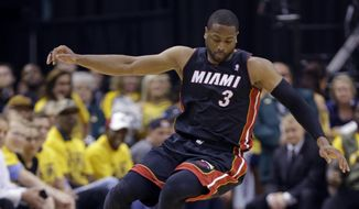 Miami Heat guard Dwyane Wade (3) goes over Indiana Pacers forward Paul George as they went for a loose ball during the fourth quarter of Game 2 of the NBA basketball Eastern Conference finals in Indianapolis, Tuesday, May 20, 2014. The Heat defeated the Pacers 87-83 to tie the series at 1-1. (AP Photo/Michael Conroy)