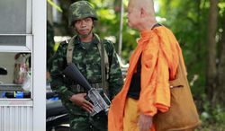 A Buddhist monk walks past a Thai soldier who provides security near the pro-government demonstration site on the outskirts of Bangkok, Thailand Wednesday, May 21, 2014. Thailand began its second day under martial law Wednesday with little visible military presence on the streets of Bangkok as residents tried to make sense of the dramatic turn of events after six months of anti-government protests and political turmoil. (AP Photo/Wason Wanichakorn)