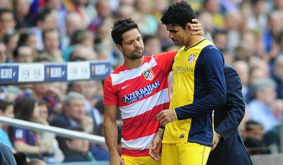 Atletico's Diego Ribas from Brazil, left, embraces teammate Diego Costa as he leaves the field after vein injured during a Spanish La Liga soccer match between FC Barcelona and Atletico Madrid at the Camp Nou stadium in Barcelona, Spain, Saturday, May 17, 2014. (AP Photo/Manu Fernandez)