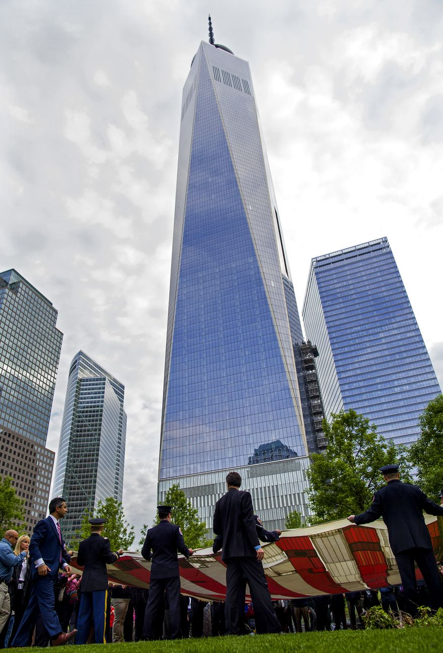 With 1 World Trade Center in the background, the National 9/11 Flag is unfurled during a ceremony at the 9/11 Memorial in New York Wednesday, May 21, 2014. Today marked the first day the 9/11 Memorial Museum was opened to the public. (AP Photo/Craig Ruttle)