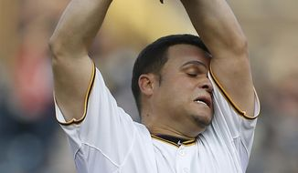 Pittsburgh Pirates starting pitcher Wandy Rodriguez (51) wipes his head as he throws against the Baltimore Orioles in the first inning of the baseball game on Wednesday, May 21, 2014, in Pittsburgh . (AP Photo/Keith Srakocic)