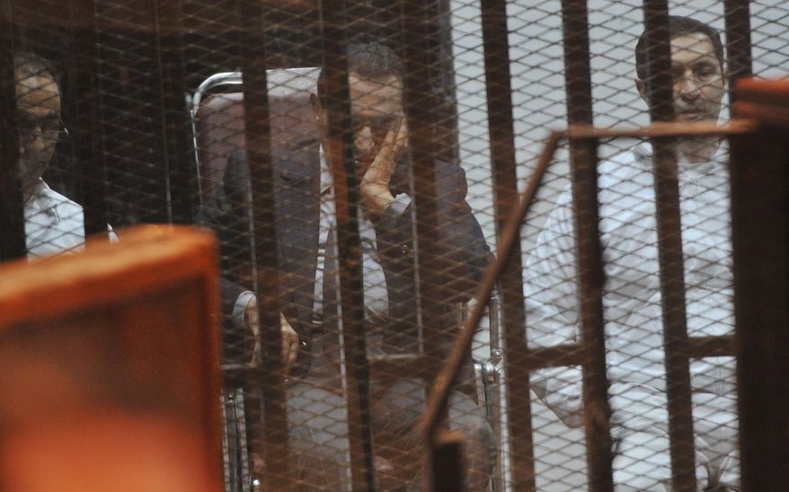 ** FILE ** In this Thursday, March 27, 2014, file photo, Egypt's ousted President Hosni Mubarak, center, and his sons Gamal, left and Alaa, right, sit inside a defendant's cage during a hearing in Cairo, Egypt. (AP Photo)