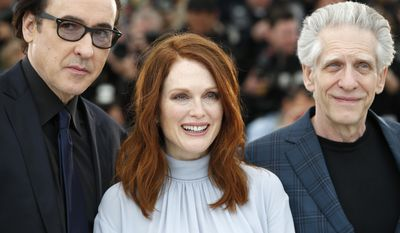 From left, actor John Cusack, actress Julianne Moore and director David Cronenberg pose for photographers during a photo call for Maps to the Stars at the 67th international film festival, Cannes, southern France, Monday, May 19, 2014. (AP Photo/Alastair Grant)