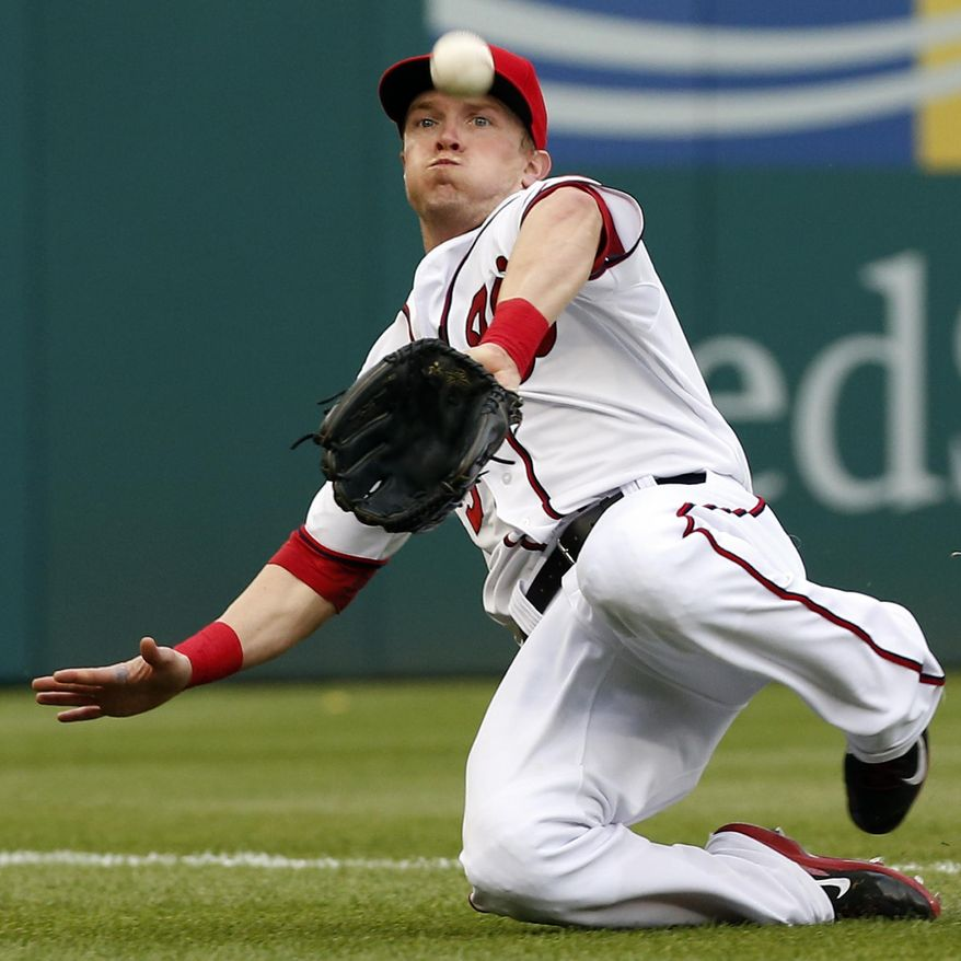 Washington Nationals left fielder Nate McLouth slides to catch a foul ball hit by Cincinnati Reds' Billy Hamilton during the fifth inning of a baseball game at Nationals Park Wednesday, May 21, 2014, in Washington. (AP Photo/Alex Brandon)