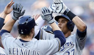 Milwaukee Brewers first baseman Mark Reynolds (7) is greeted at home plate by teammate  Carlos Gomez (27) after hitting a grand-slam home run in the first inning of a baseball game against Atlanta Braves Wednesday, May 21, 2014,2 in Atlanta.(AP Photo/John Bazemore)