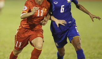 Vietnam's Nguyen Thi Nguyet , left, vies for the ball with Thailand's Pikul Khueanpet, during their AFC Women's Asian Cup soccer match at Thong Nhat Stadium in Ho Chi Minh City, Vietnam, Wednesday, May 21, 2014. Thailand won 2-1. (AP Photo/Achmad Ibrahim)