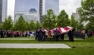 ** FILE ** The National 9/11 Flag is unfurled during a ceremony at the 9/11 Memorial in New York Wednesday, May 21, 2014.  The ceremony Wednesday marked the opening of the National September 11 Memorial Museum. After the flag was refolded, firefighters marched it into the museum. The flag was flying from a building near the World Trade Center on Sept. 11, 2001. It was later found shredded in the debris of ground zero.  (AP Photo/Craig Ruttle)
