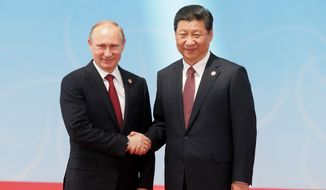 Russia's President Vladimir Putin, left, and China's President Xi Jinping shake hands before posing for a photo during the fourth Conference on Interaction and Confidence Building Measures in Asia (CICA) summit, in Shanghai, China, Wednesday, May 21, 2014.  (AP Photo/RIA Novosti, Mikhail Metzel, Presidential Press Service)