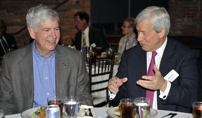 Michigan Gov. Rick Snyder, left, speaks with JP Morgan Chase Chairman and CEO  Jamie Dimon at an announcement, Wednesday May 21, 2014, about Chase investing$100 million in Detroit over the next five years. (AP Photo/Detroit News, Chrles V. Tines)