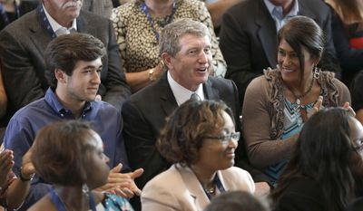Bill Elliott, center, smiles with son Chase Elliott, left, and wife, Cindy, right, after being named as one of five inductees into the NASCAR Hall of Fame class of 2015, in Charlotte, N.C., Wednesday, May 21, 2014. (AP Photo/Chuck Burton)