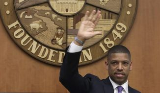 Sacramento Mayor Kevin Johnson waves to Vivek Ranadive, majority owner of the Sacramento Kings after the Sacramento City Council approved a financing plan for a new arena for the NBA basketball team, in  Sacramento, Calif., Tuesday, May 20, 2014.  The council voted 7-2 on the package that clears the way for construction of a $477 million downtown arena.(AP Photo/Rich Pedroncelli)