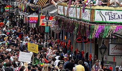 Crowds congregate on Bourbon Street for festivities outside the Royal Sonesta Hotel in the French Quarter on Mardi Gras day in New Orleans, Tuesday, March 8, 2011. (AP Photo/Gerald Herbert)