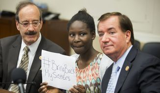 Deborah Peter, center, holds up a sign, flanked by House Foreign Affairs Committee Chairman Rep. Ed Royce, R-Calif. right, and the committee's ranking member Rep. Eliot Engel, D-N.Y. during a pre-hearing medial availability on Capitol Hill in Washington, Wednesday, May 21, 2014. Peter, is a sole survivor of a Dec. 11, 2011, Boko Haram attack on her household, where her father and brother were killed for not renouncing their Christian faith.  (AP Photo/Manuel Balce Ceneta)