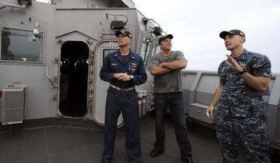"This May 20, 2014 photo released by TNT shows actor Adam Baldwin from the new TNT series ""The Last Ship,"" center, getting a tour of the bridge deck from Cmdr. Scott Bowman of the USS Oak Hill en route to New York Harbor for Fleet Week celebrations. On Tuesday, Baldwin hosted a special screening of the series aboard the dock landing ship. The series, also starring Eric Dane and Rhona Mitra, premieres on Sunday, June 22, at 9 p.m. ET. (AP Photo/TNT, E. M. Pio Roda)"