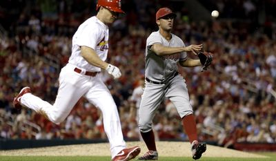 Arizona Diamondbacks relief pitcher Randall Delgado, right, throws St. Louis Cardinals' Mark Ellis,left, out at first during the eighth inning of a baseball game Thursday, May 22, 2014, in St. Louis. (AP Photo/Jeff Roberson)