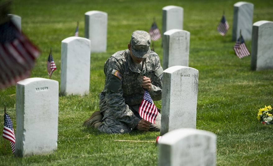 """Army Pvt. II Dylan Conway, 19, of Mason, Mich., of the 3rd U.S. Infantry Regiment, also known as The Old Guard, places flags at grave sites at Arlington National Cemetery in Arlington, Va., Thursday, May 22, 2014, as part of the annual """"Flags-In"""" ceremony in preparation for Memorial Day. (AP Photo/Cliff Owen)"""