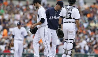 Detroit Tigers starting pitcher Robbie Ray, left foreground, is relieved by manager Brad Ausmu, center, as catcher Alex Avila looks on, during the fourth inning of a baseball game against the Texas Rangers  in Detroit, Thursday, May 22, 2014. (AP Photo/Carlos Osorio)