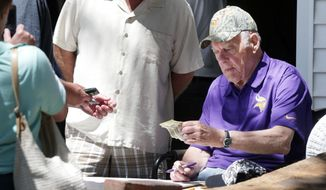Former Minnesota Vikings head football coach Bud Grant excepts cash during his three-day rummage sale,Thursday, May 22, 2014 at his Bloomington, Minn., home. Grant will be 87 next week.  (AP Photo/Jim Mone)