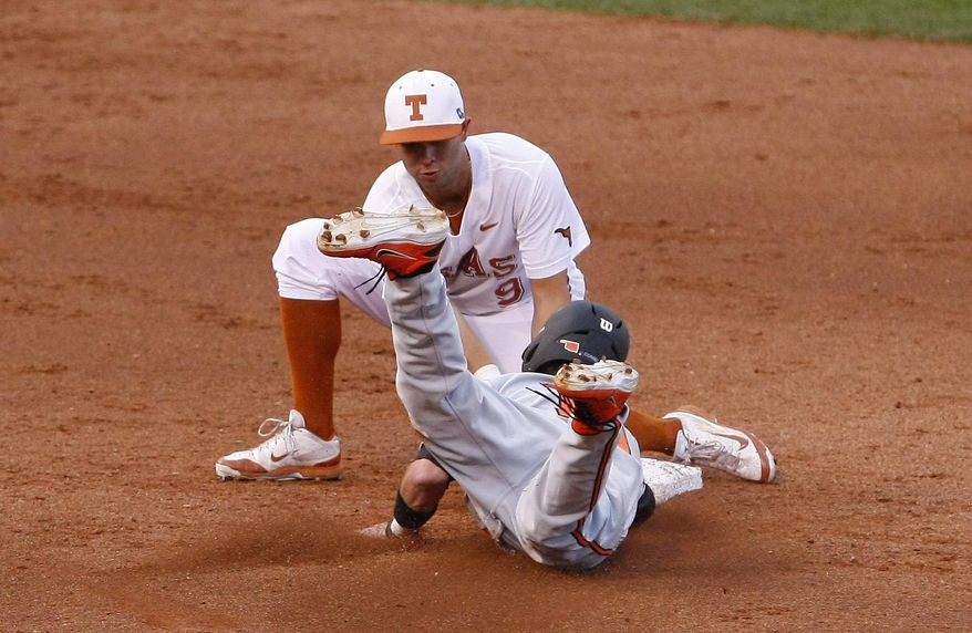 Texas short stop C.J. Hinojosa tags out Oklahoma State Aaron Cornell at second in the second inning of a second-round game in the Big 12 conference NCAA college baseball tournament in Oklahoma City, Thursday, May 22, 2014. (AP Photo/Alonzo Adams)