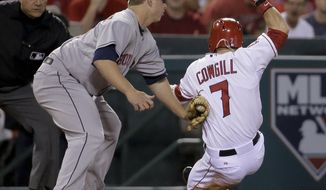 Houston Astros third baseman Matt Dominguez tags Los Angeles Angels' Collin Cowgill at third base as Cowgill tried to advance on a single by Howie Kendrick during the fifth inning of a baseball game in Anaheim, Calif., Wednesday, May 21, 2014. (AP Photo/Chris Carlson)