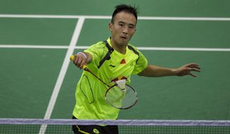 China's Du Pengyu returns a shot to Thailand's Tanongsak Saensomboonsuk during their quarter final match of men's singles event at the Thomas Cup Badminton in New Delhi, India, Thursday, May 22, 2014. (AP Photo/Tsering Topgyal)