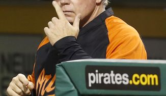 Baltimore Orioles manager Buck Showalter gives signals from the dugout with his team at bat with two runners on base in the seventh inning inning of a baseball game against the Pittsburgh Pirates on Wednesday, May 21, 2014, in Pittsburgh. The Pirates won 9-8. (AP Photo/Keith Srakocic)