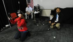 In this Friday May 16, 2014, photo, Cummins engineers Bill Tuttle and Sushant Dhiman watch as Greenwood Middle School student Heaven Carmichel, 14, looks at a locomotive engine using a virtual reality computer-aided drafting system. The software allows engineers to virtually walk through large projects. (AP Photo/The Daily Journal, Scott Roberson)