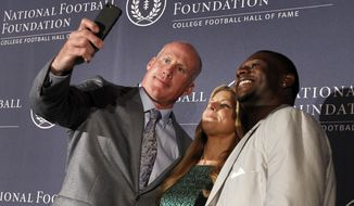 Former Penn State linebacker Shane Conlan, left, and former TCU tailback LaDainian Tomlinson, right, pose for selfie with event emcee Bonnie Bernstein, center, after Conlan and Tomlinson were introduced as 2014 inductees at a National Football Foundation College Football Hall Of Fame news conference, Thursday, May 22, 2014, in Irving, Texas. (AP Photo/Tony Gutierrez)