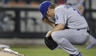 Los Angeles Dodgers starting pitcher Zack Greinke adjusts his cap between batters during the fifth inning of a baseball game against the New York Mets, Thursday, May 22, 2014, in New York. (AP Photo/Julie Jacobson)