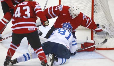 Canada's Nazem Kardi, left, Ben Scrivens and Finland's Irio Pakarinen battle for the puck during the Group A Quarterfinal match at the Ice Hockey World Championship in Minsk, Belarus, Thursday, May 22, 2014. (AP Photo/Sergei Grits)